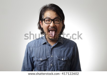 The asian man in blue denim shirt is showing his tongue.