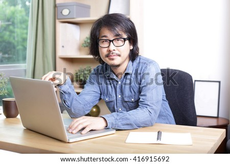 The asian man in blue denim shirt is using computer.