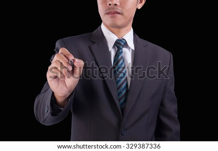 The Asian successful business man will write his signature, on black background. - stock photo