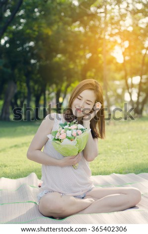 The Asian woman  smiling and looking rose flower, Feel happy and enjoy at tree park. - stock photo