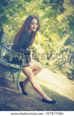 The Asian women sitting in a park wearing a black dress, smiling shyly alone on a couch behind a green blur bokeh.look vintage tone.