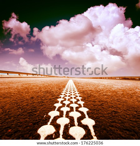 the asphalt road to horizon with cloudy sky - stock photo