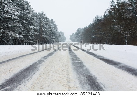 The asphalted road covered with snow. On road some strips from wheels of cars are visible - stock photo