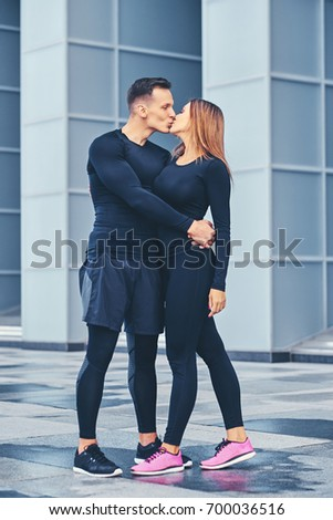 The athletic fitness couple modern building background.