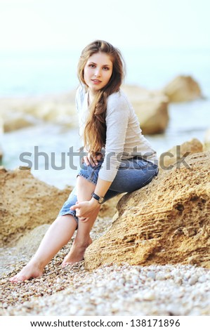 The attractive bright girl sits on the bank of a beach smiles