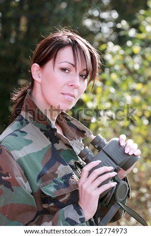 The attractive girl in a camouflage with a binoculars - stock photo