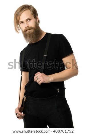 the attractive man the blonde with long hair of the European appearance with a beard holds braces in a black t-shirt and black trousers on a white background - stock photo
