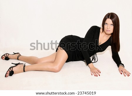 The attractive young girl in a black dress in a pose lying on a white background