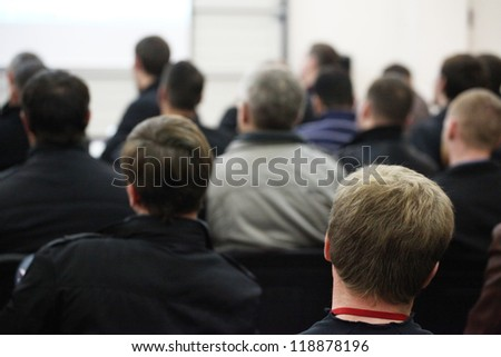 The audience listens to the acting in a conference hall. - stock photo