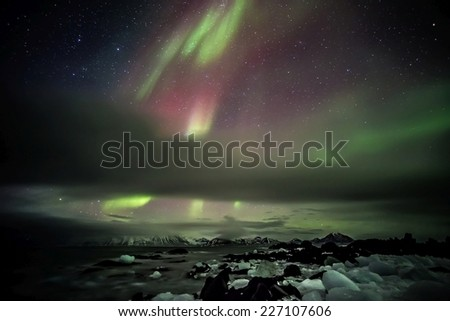 The aurora borealis or the northern lights in the Arctic - stock photo