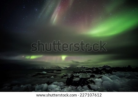 The aurora borealis or the northern lights over the Arctic fjord - stock photo