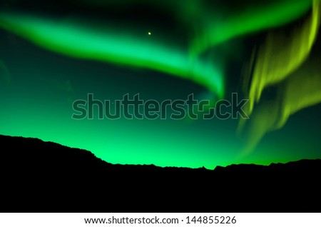 The aurora borealis over the mountain and lake in iceland - stock photo