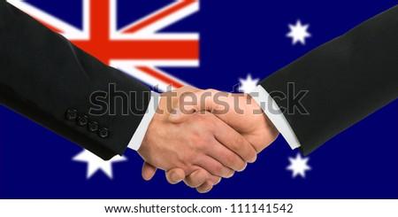 The Australian flag and business handshake - stock photo