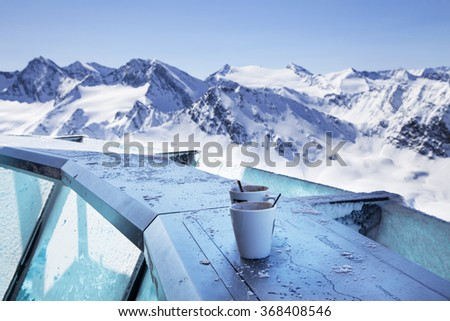 The austrian Alps mountain panorama view from the restaurant terrace with the coffee cups in front - stock photo