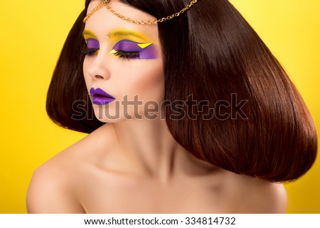 The avantaged portrait,girl with an unusual make up looking at the camera,portrait on a yellow backgraund,custom volume hairstyle metal ornament in the form of fragments,fashionable toning,creative  - stock photo