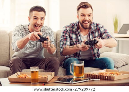 The avid gamers. Two young happy men playing video games while sitting on sofa - stock photo