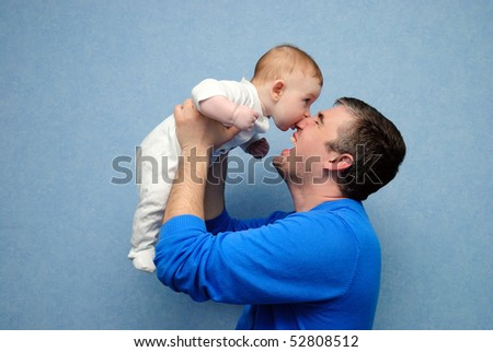 The baby bites the daddy nose. The daddy laughs