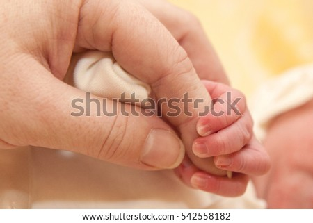 The baby clings to his mother's finger