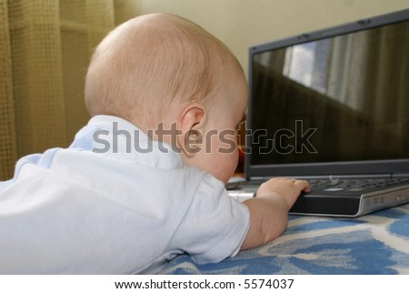 The baby creeps to a computer - stock photo