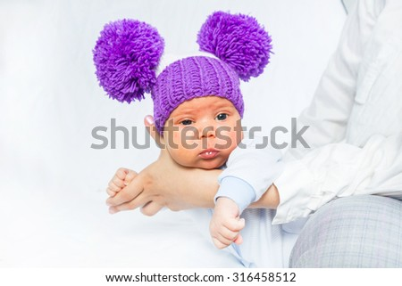 The baby in a lilac knitted hat with big pompons - stock photo