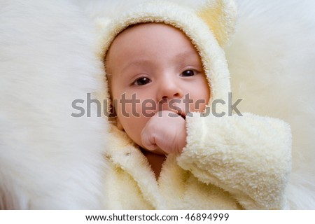 The baby is dressed in a suit of a bear cub
