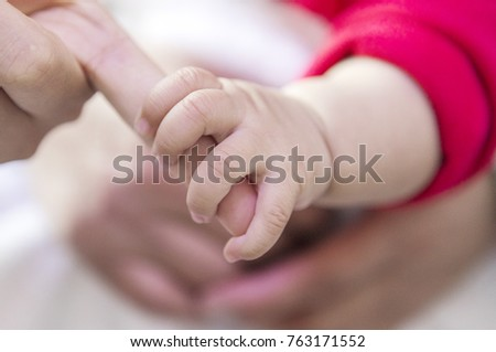 The baby is holding its mother's finger