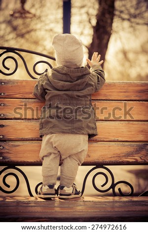 the baby is in fashionable clothes on the bench - stock photo