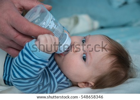 The baby is the third month from birth drink water from a bottle. Dad gives baby a bottle.