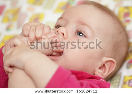 The baby pulls a foot in a mouth - stock photo