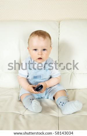 The baby sits on a white sofa with the TV panel - stock photo