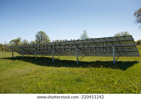 The back of a solar panel set on a meadow - stock photo