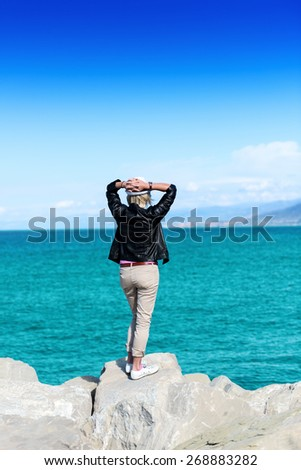 The back of an attractive young woman looking at the ocean view - stock photo