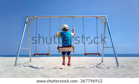 The back of the boys Swings are playing on the beach, sea and sky, bright sun .