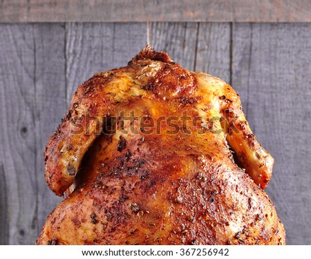 The back of whole roasted chicken with spices o wood background - stock photo