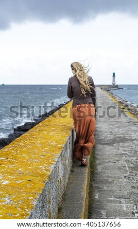The back view of a girl walking down the long stone pier, yellow line, windy day, lighthouse - stock photo