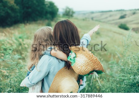 The back view of young mother and daughter with hats on green grass background  - stock photo