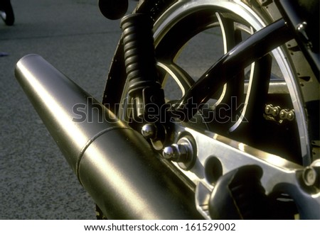 The back wheel of a motorcycle with the exhaust pipe. - stock photo