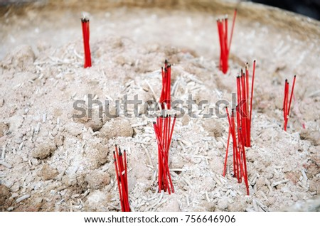 The background image of red incense sticks with white ashes under at front of temple.