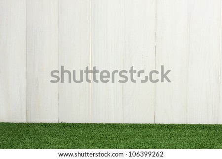 The background of green grass against the white barn