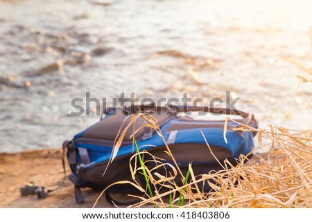 The backpack lies on a stone against water flow. The dry grass in the foreground, a backpack of blue color, a scene is lit with the sunset sun - stock photo