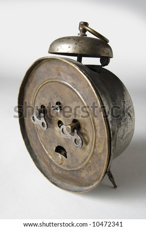 The backside of an old alarm-clock. Clockwork keys. - stock photo