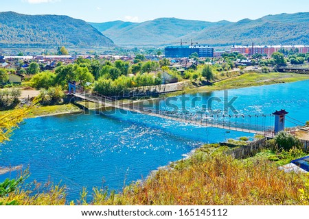 The Bahrain Yalu river and steel cable bridge.The photo taken in China's inner mongolia autonomous region hulun buir city yakeshi bahrain town, Lama (buddhist monk) mountain national forest park. - stock photo