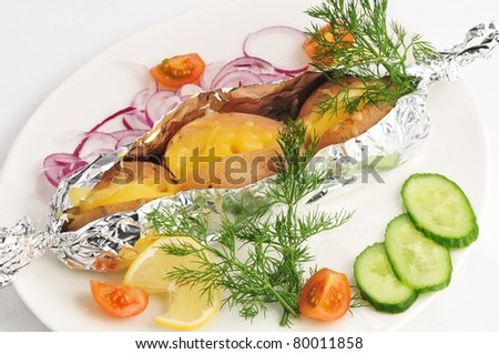 The baked potato in a foil with a garnish on a white plate - stock photo