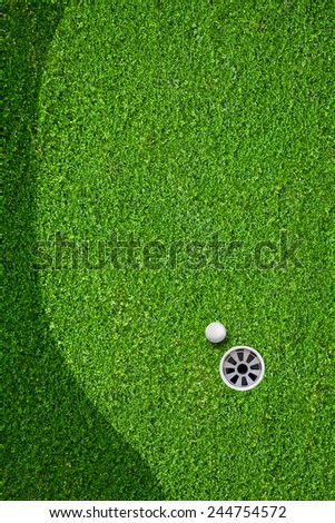 The ball at the hole on the golf course - stock photo