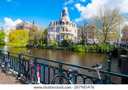 The bank of the Singelgrachtkering Canal with bikes in Amsterdam, the Netherlands. - stock photo