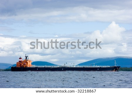 The barge moving on a gulf against hills - stock photo