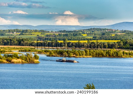 The barge with the sand on the lake - stock photo