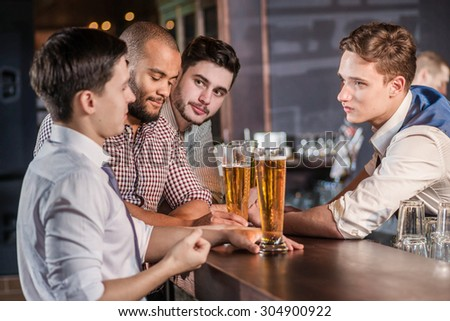 The bartender takes orders for beer. Three cheerful friend makes ordering a beer from the bartender at the bar