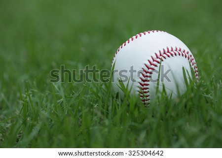 The Baseball ball standard hard cork inner size diameter 7.28 CM hand sewing made from leather and weight 130 - 150 grame, isolated on green grass.