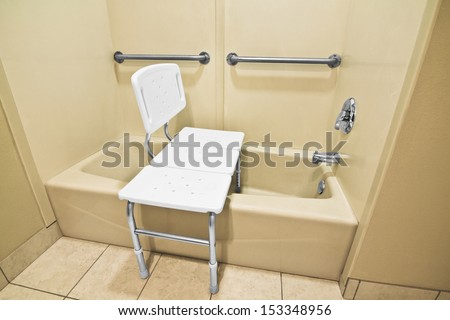 The bathing chair helps the disabled and handicap use the bathtub easier with access at the height of a wheelchair. The wall handles help with accessibility.  - stock photo